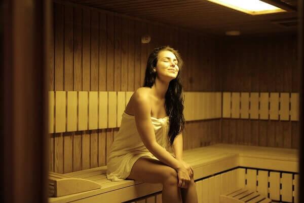 A beautiful woman sitting in a sauna