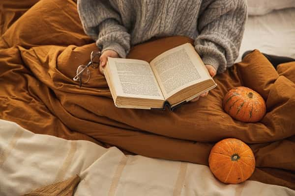 person in bed, reading a book, covered with a blanket
