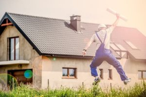 A contractor jumping excitedly while holding a plan
