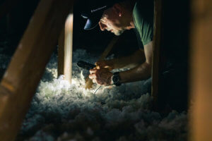 Man working in the dark attic of a house with a headlamp for the light source.